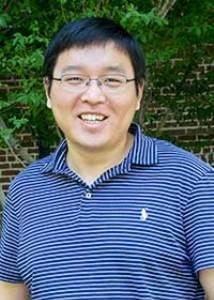 A smiling Lei Yang in glasses and a blue-striped polo shirt