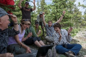 Nexus Graduate Student Leadership participants hold arms up triumphantly on a hiking path.