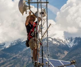 A man installs monitoring equipment atop an antennae tower