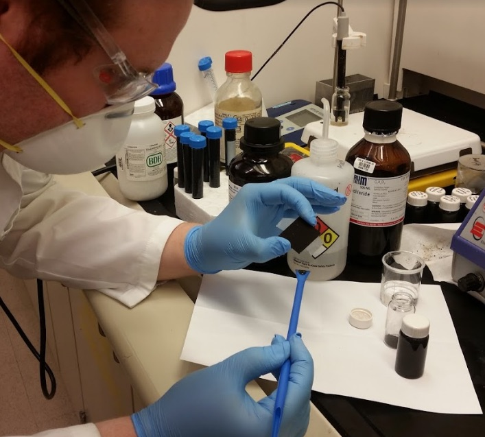 Dale Karas carefully works with chemicals in a lab