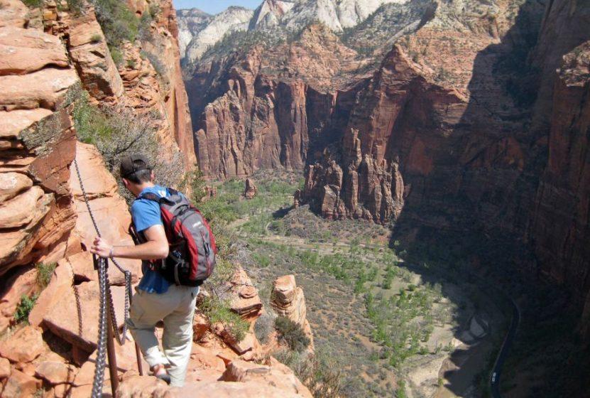 A hiker grips a chain railing as he follows a path along the edge of a cliff.