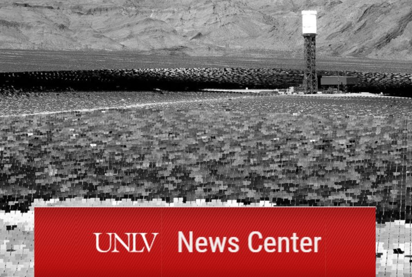 Black and white photo of a solar farm in a desert valley.