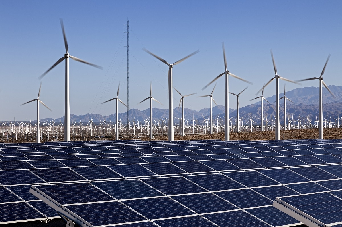 A field of solar panels and wind turbines