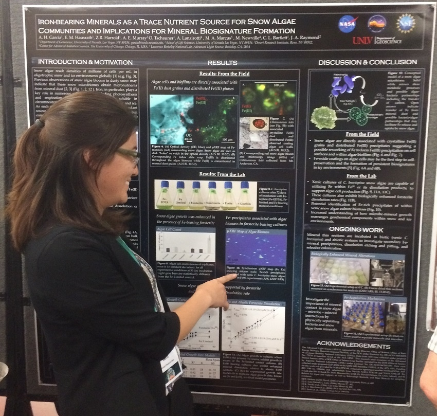 A UNLV student excitedly points at her science poster on Iron-Bearing Minerals As a Trace Nutrient Source For Snow Algae Communities And Implications for Mineral Biosignature Formation