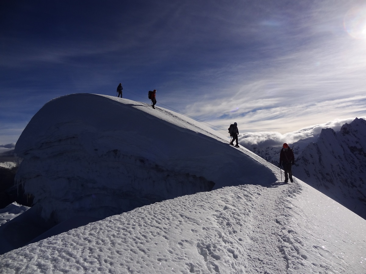 Four mountaineers are silhouetted against a twilight sky on a snowy summit