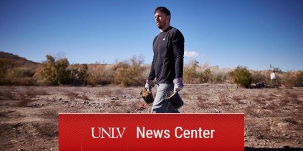 Dr. Scott Abella strides through a desert landscape. He holds potted desert vegetation in each hand.